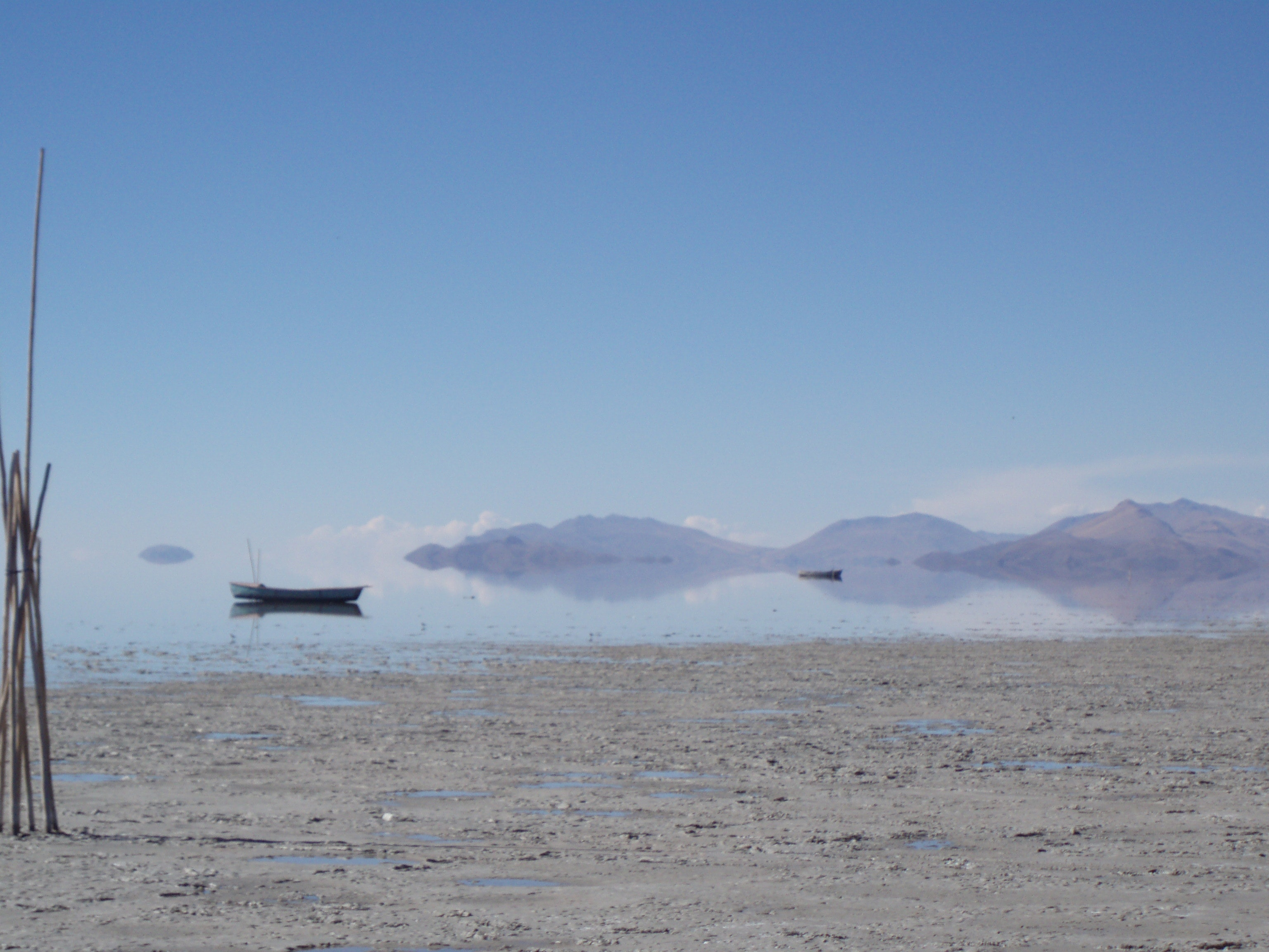 Dried shore, boats on lake, hills in distance.